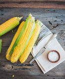 Fresh corn on cobs on a wooden surface, whole plant foods, top v Stock Photo