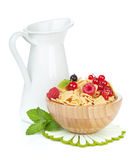 Fresh corn flakes with berries and milk jug. Isolated on white background Royalty Free Stock Photo