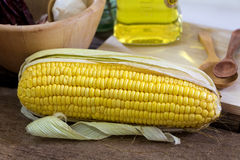Fresh corn, garlic and wooden bowl on the wood table. Close-up Stock Image