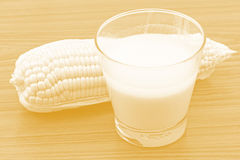 Fresh corn juice in glass and corn cobs on grunge wood Royalty Free Stock Photography