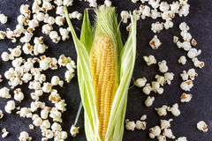 Fresh corn and popcorn on black table Stock Images