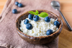 Fresh cottage cheese and blueberries. Cottage cheese (quark) with fresh blueberries decorated with mint. Healthy country breakfast Royalty Free Stock Image