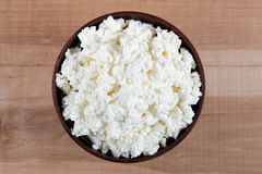 Fresh cottage cheese in a bowl on a wooden table Stock Photography