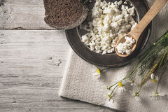 Fresh cottage cheese with bread and flowers on the white wooden table top view Stock Photo