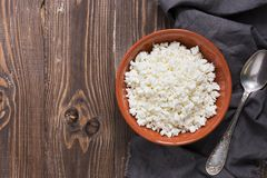 Fresh cottage cheese in a ceramic bowl on a rustic wooden background, top view. Royalty Free Stock Image