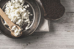 Fresh cottage cheese on the  metal plate  with bread on the white wooden table Royalty Free Stock Photos