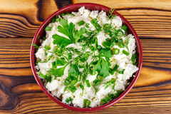 Fresh cottage cheese with sour cream, dill, parsley, onion in ceramic bowl on wooden table, top view Stock Images