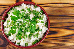 Fresh cottage cheese with sour cream, dill, parsley, onion in ceramic bowl on wooden table, top view Stock Photography