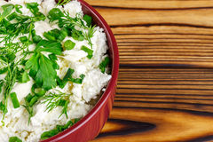 Fresh cottage cheese with sour cream, dill, parsley, onion in ceramic bowl on wooden table, top view Stock Image