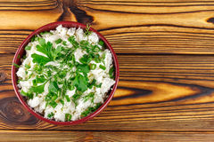 Fresh cottage cheese with sour cream, dill, parsley, onion in ceramic bowl on wooden table, top view Royalty Free Stock Image
