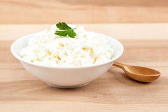Fresh cottage cheese in a white bowl with wooden spoon. Royalty Free Stock Photo