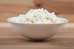 Fresh cottage cheese in a white bowl on a wooden table Royalty Free Stock Photo