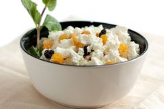 Fresh cottage cheese with yellow and blue raisins. In a round white bowl Royalty Free Stock Images