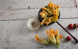 Fresh courgette flower. S, chili peppers and onion on white table royalty free stock photos