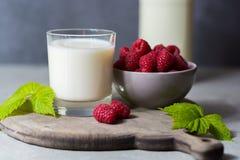 Fresh cow milk and ripe organic red raspberry Stock Image
