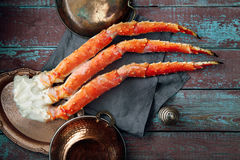 Fresh crab claws on vintage wooden background. With copper plates and lemon slices. Composition with copy space Royalty Free Stock Images