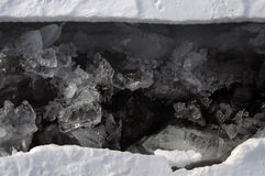 Fresh crack broke the thick ice. Fresh clean water rises from the depths and freeze in the cold. Ice Storm. Ice hummocks on the northern shore of Olkhon Island Stock Photo