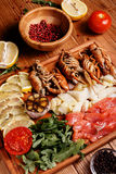 Fresh crayfish, red and white pangasius fish fillet. Decorated with arugula, tomatoes, lemon, garlic and spice on a wooden board. Seafood platter Stock Photo