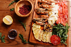Fresh crayfish, red and white pangasius fish fillet. Decorated with arugula, tomatoes, lemon, garlic and spice on a wooden board. Seafood platter Royalty Free Stock Photography
