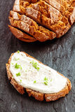Fresh cream cheese with herbs. Served on a slice of wholesome rye bread viewed from above on a dark textured surface alongside the slice rye loaf Royalty Free Stock Photo