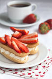 Fresh cream eclairs with whipped cream and strawberries and cup Stock Photography