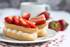 Fresh cream eclairs with whipped cream and strawberries and cup Royalty Free Stock Image