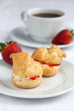 Fresh cream puff with whipped cream and strawberries on white pl Stock Photos