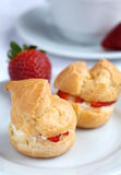 Fresh cream puff with whipped cream and strawberries on white pl Royalty Free Stock Photography
