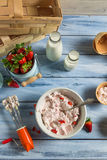 Fresh cream and strawberries as ingredients for ice cream. On old wooden table stock photo