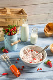 Fresh cream and strawberries as ingredients for ice cream. On old wooden table royalty free stock images