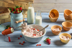 Fresh cream and strawberries for ice cream. Fresh cream and strawberries as ingredients for ice cream on old wooden table royalty free stock images