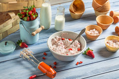 Fresh cream and strawberries for ice cream. Fresh cream and strawberries as ingredients for ice cream on old wooden table Stock Photos