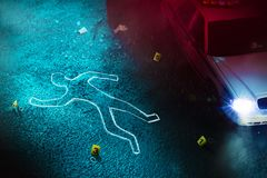Fresh crime scene with body silhouette. Crime scene with body outline, evidence markers and a police car with dramatic lighting royalty free stock images