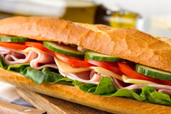 Fresh crispy baguette filled with ham, crunchy lettuce, sweet tomatoes, juicy cucumber, aromatic cheese and mayonnaise Royalty Free Stock Images