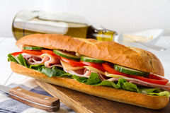 Fresh crispy baguette filled with ham, crunchy lettuce, sweet tomatoes, juicy cucumber, aromatic cheese and mayonnaise Stock Photography