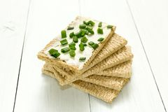 Fresh crispy bread with cottage cheese and green onion on a white wooden table. Dietary breakfast royalty free stock images