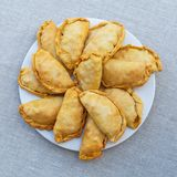 Fresh, crispy, puff pies on a white plate. View from above. Fresh, crispy, puff pies on a white plate standing on a linen tablecloth. View from above Royalty Free Stock Photo