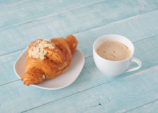Fresh croissant with almonds and cup of coffee with milk Stock Photo
