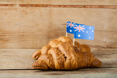 Fresh croissant and australian flag. On wood desk Stock Photos
