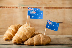 Fresh croissant and australian flag. On wood desk Royalty Free Stock Photo