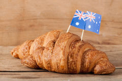 Fresh croissant and australian flag on wood desk. Greeting card Royalty Free Stock Photo