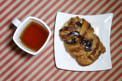 Fresh croissant with chocolate on white plate. White tea cup. Fresh croissant with chocolate on white plate. White tea cup Royalty Free Stock Photo