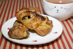 Fresh croissant with chocolate on white plate. White tea cup. Fresh croissant with chocolate on white plate. White tea cup Stock Image