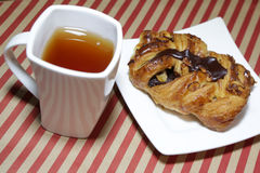 Fresh croissant with chocolate on white plate. White tea cup. Fresh croissant with chocolate on white plate. White tea cup Stock Photo