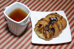 Fresh croissant with chocolate on white plate. White tea cup. Fresh croissant with chocolate on white plate. White tea cup Stock Photography
