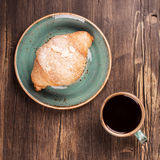 Fresh croissant and cup of black coffee Stock Photos