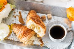 Fresh Croissant, Cup of Coffee and Ranunculus Flowers. Breakfast. Breakfast in Bed from fresh Croissant and Cup of Coffee on the grey tray, Ranunculus Flowers Royalty Free Stock Image
