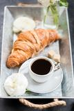 Fresh Croissant, Cup of Coffee and Ranunculus Flowers. Breakfast. Light Breakfast from fresh Croissant and Cup of Coffee on the grey tray, Ranunculus Flowers Stock Photo