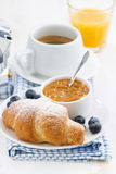 Fresh croissant with orange jam, blueberries and coffee. For breakfast, closeup, vertical Royalty Free Stock Images