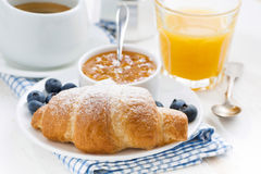 fresh croissant with orange jam, blueberries and coffee Royalty Free Stock Photos